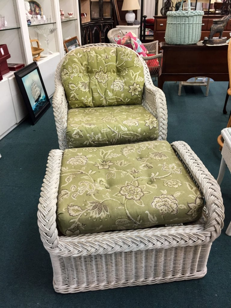 White Wicker Chair w/Ottoman • White wicker chair and white wicker ottoman. Lovely green and white flowered fabric. This piece would be a great addition to a sunroom.