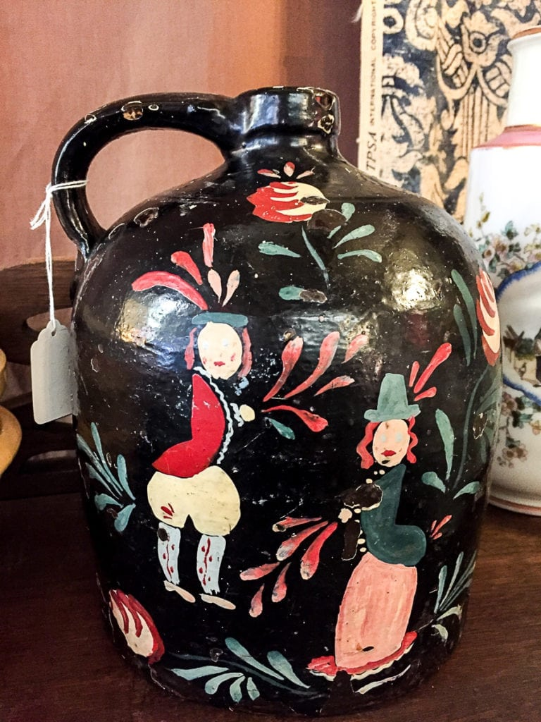 Folk Art Jug - Vintage • Vintage hand painted black folk art jug with characters. This black jug with accents of red will liven up any buffet in a dining room or give your bookshelf some pizazz. A unique item that is not found in mass market stores.