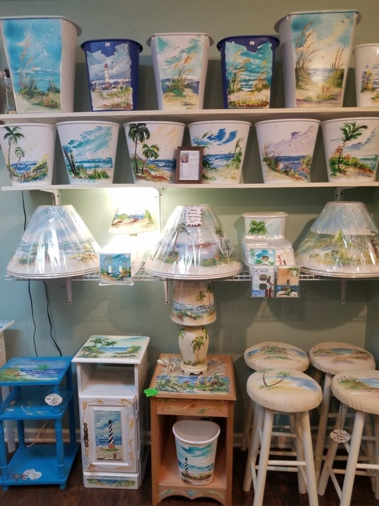 Hand painted home decor • This local artist paints beautiful beach scenes. You can choose from furniture, lampshades, lamps, landscapes on windows and a large assortment of switchplate covers. If you need a custom piece done, no problem.
