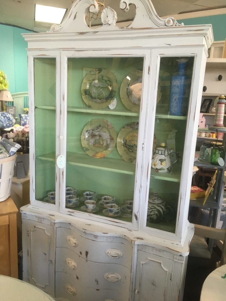 Chalk Paint China Cabinet • Antique china cabinet in a faint blue chalk paint with a pleasing green interior to showcase your china or favorite ceramics. Features an ornate scroll top, plate grooves and storage underneath for silverware & napkins.