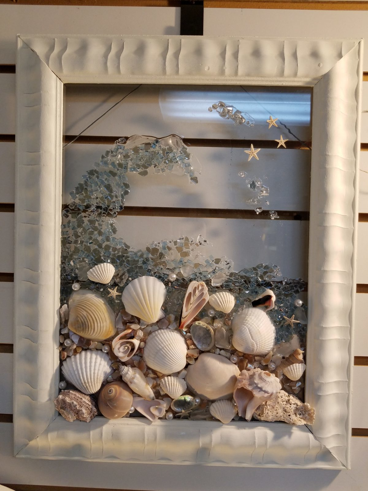 """Shell wave on glass. • This local artisan has many pieces in our store.  I am sharing my favorite. This piece measures 14""""x18"""". Beautiful shells in resin to simulate a wave. She also has alot of pieces where she incorporates mermaids."""