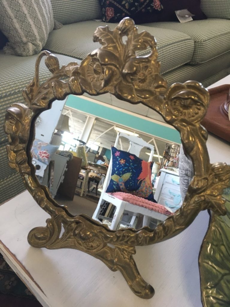 Vintage Brass Vanity Mirror • Vintage brass standing vanity mirror on easel is made of heavy brass with an attractive floral design surrounding the oval shaped mirror. Wonderful, thoughtful gift sure to add a touch of elegance to any table, vanity or bathroom.