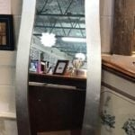 "Bassett Chevel mirror • Look at those curves! This mirror would be lovely hung vertically in a dressing room or hang it horizontally over a buffet in the dining room or fireplace. Silver frame. Measures 62""x16"""