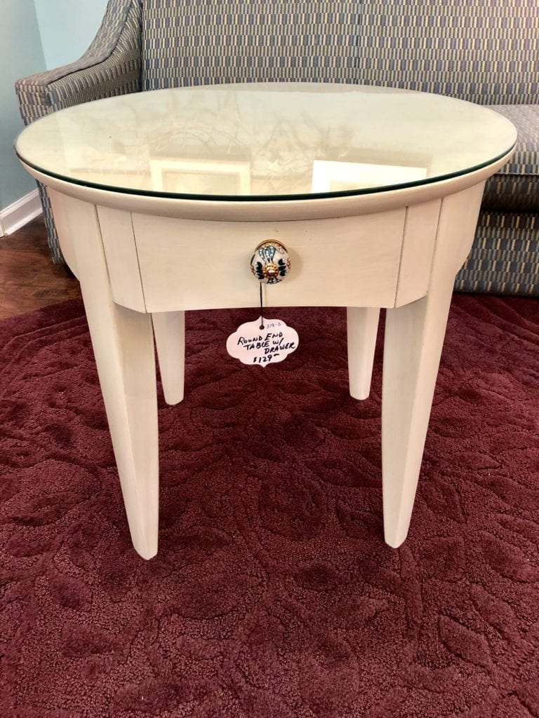 Round Offwhite End Table w/drawer • Nice offwhite round end table with drawer. Knob is unique and adds a splash of color. Glass is included to keep top of end table nice.
